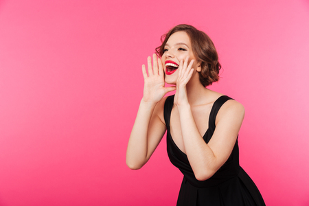 Portrait of a happy girl dressed in black dress shouting and looking away isolated over pink background