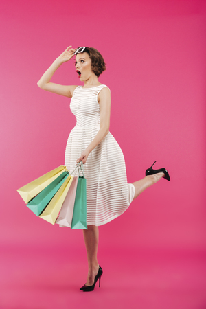 Full length portrait of a shocked girl dressed in dress holding shopping bags and looking away isolated over pink background