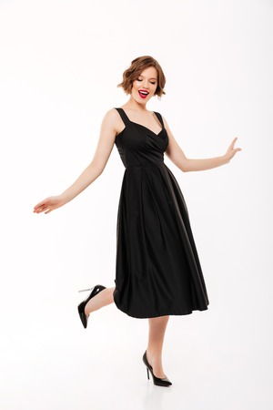 Full length portrait of a lovely girl dressed in black dress posing while walking isolated over white background