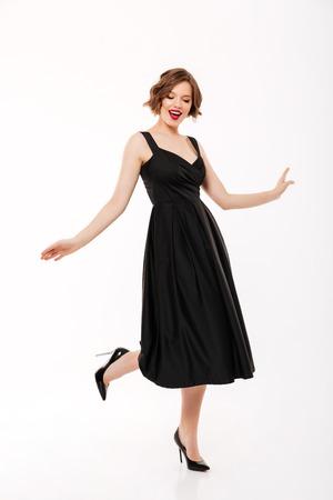 pleine longueur portrait d & # 39 ; une belle fille habillée en robe noire posant tout en marchant isolé sur fond blanc