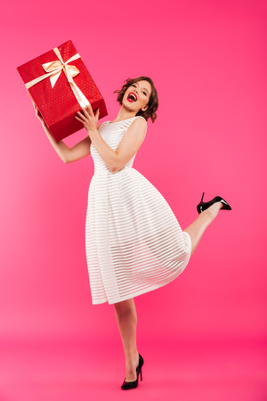Full length portrait of a joyful girl dressed in dress holding gift box while standing isolated over pink background Foto de archivo