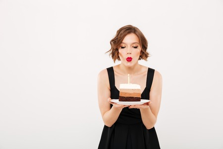 Portrait of a pretty girl holding plate with a piece of birthday cake and blowing a candle isolated over white background Imagens