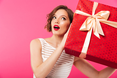 Portrait of a pretty girl dressed in dress holding gift box at her ear while standing isolated over pink background