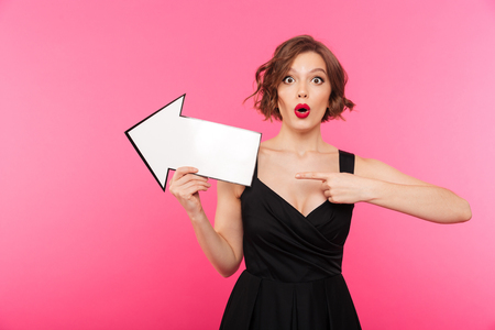 Portrait of a surprised girl dressed in black dress pointing away with an arrow isolated over pink background Stock Photo - 95007279