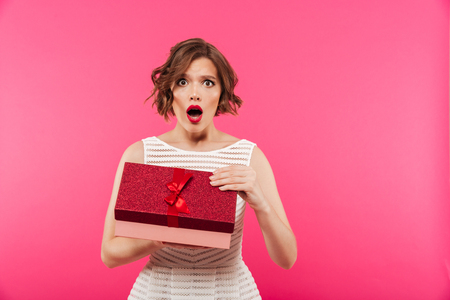 Portrait of a surprised girl dressed in dress opening a gift box and looking at camera isolated over pink background