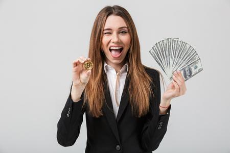 행복 한 사업가의 초상화 돈 지폐를 잔뜩 들고 회색 배경 위에 절연 황금 bitcoin을 보여주는 양복을 입고