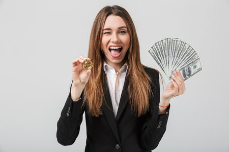 Portrait of a happy businesswoman dressed in suit holding bunch of money banknotes and showing golden bitcoin isolated over gray background