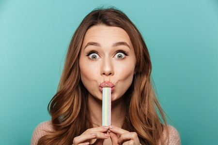 Beauty portrait of a cute brown haired woman with sparkling makeup eating sugar candy isolated over blue background Фото со стока