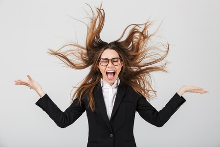 Portrait of an angry businesswoman dressed in suit screaming isolated over gray background Stock Photo