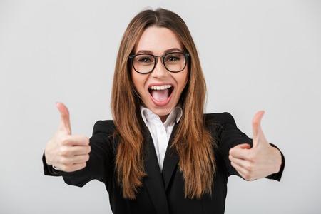 회색 벽 위에 절연 엄지 손가락을 보여주는 businesswear에 행복 쾌활한 아가씨 스톡 콘텐츠