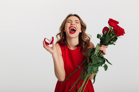 Portrait of an excited young woman dressed in red dress holding box with engagement ring and bouquet of roses while standing and celebrating isolated over white background Stock Photo