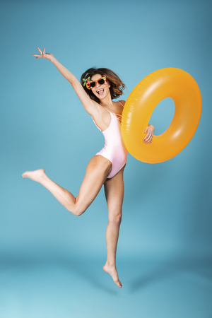 Full length portrait of a cheerful girl dressed in swimsuit and sunglasses holding inflatable ring and jumping isolated over blue background 免版税图像