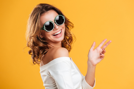 Photo of happy young woman isolated over yellow background. Looking camera pointing.