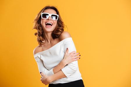 Foto van opgewekte gelukkige jonge vrouw status geïsoleerd over gele achtergrond. Zoek camera.