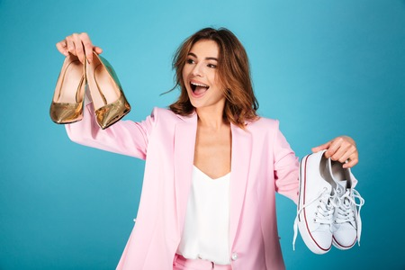 Portrait of a happy woman dressed in pink suit holding pair of high heels shoes and pair of sneakers isolated over blue background