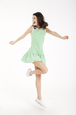 Full length portrait of a cheerful girl in dress posing while standing on tiptoes isolated over white background