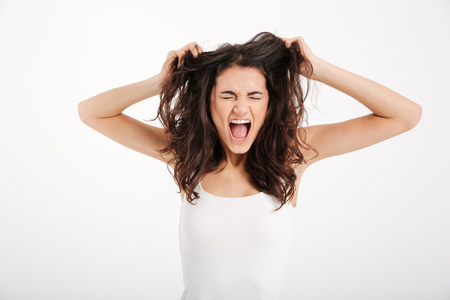 Portrait of a mad girl dressed in tank-top pulling her hair out and screaming isolated over white background Stock Photo