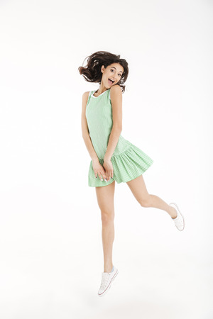 Full length portrait of a joyful girl dressed in dress posing while jumping on tiptoes and looking at camera isolated over white background