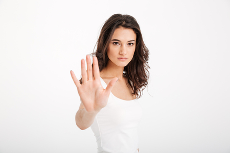 Portrait of a serious girl dressed in tank-top showing stop gesture with her arm isolated over white background Stock Photo