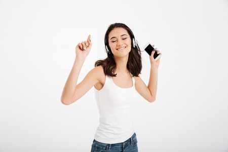 Portrait of a delighted girl dressed in tank-top listening to music with headphones while holding mobile phone and dancing isolated over white background