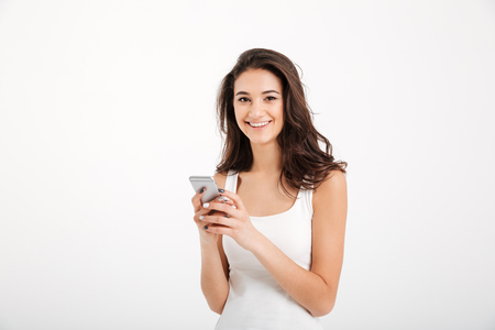 Portrait of a smiling girl dressed in tank-top holding mobile phone isolated over white background