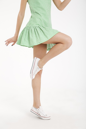 Half body portrait of a young girl in dress posing while standing on one leg isolated over white background