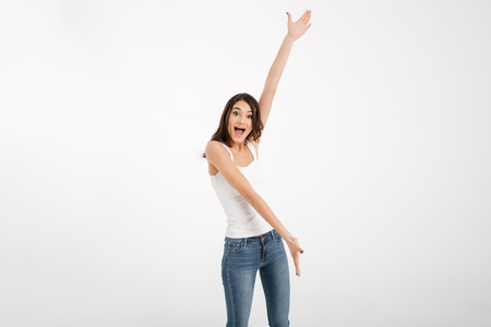 Portrait of a joyful girl dressed in tank-top presenting copy space isolated over white background
