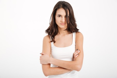 Portrait of an upset girl dressed in tank-top standing with arms foded and looking at camera isolated over white background Stock Photo