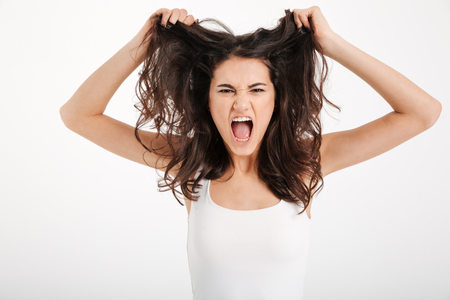 Portrait of an angry girl dressed in tank-top pulling her hair out and screaming isolated over white background Stock Photo