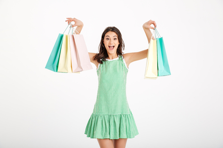 Portrait of an attractive girl in dress holding shopping bags and screaming isolated over white background