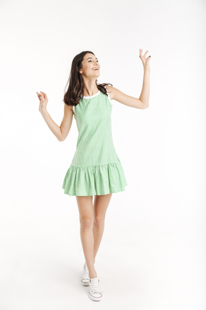 Full length portrait of a cheerful girl dressed in dress posing while standing on tiptoes and looking away isolated over white background