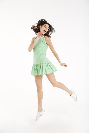 Full length portrait of a pretty girl dressed in dress posing while jumping on tiptoes and looking away isolated over white background Stock Photo