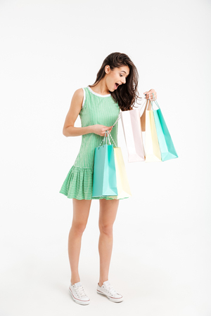 Full length portrait of a lovely girl in dress looking inside shopping bags isolated over white background Stock Photo