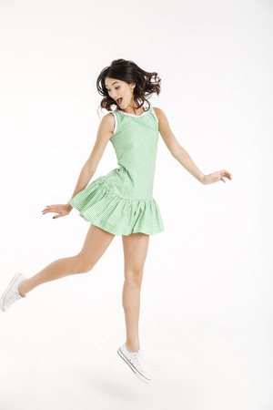 Full length portrait of a happy girl dressed in dress posing while jumping on tiptoes and looking away isolated over white background