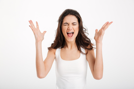 Portrait of a furious girl dressed in tank-top screaming isolated over white background Stock Photo