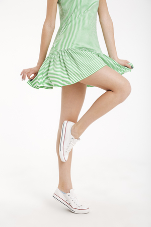 Half body portrait of a young girl in dress posing on one leg isolated over white background