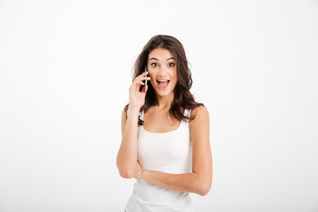 Portrait of a surprised girl dressed in tank-top talking on mobile phone isolated over white background Stock Photo
