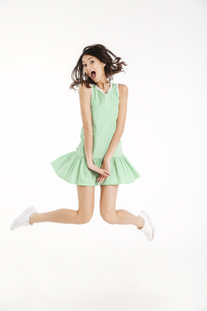 Full length portrait of a funny girl dressed in dress posing while jumping on tiptoes and looking at camera isolated over white background
