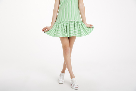 Half body portrait of a young girl in dress posing with legs crossed isolated over white background