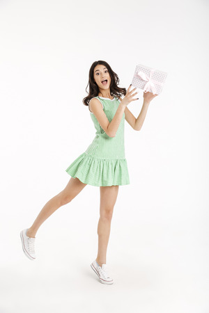 Full length portrait of a joyful girl dressed in dress standing and holding gift box isolated over white background