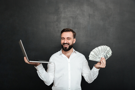 Portrait of cheerful rich man in white shirt winning lots of money dollar currency using his notebook over dark gray background