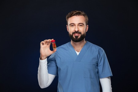 Portrait of a smiling male doctor dressed in uniform holding container with urine sample isolated over dark background