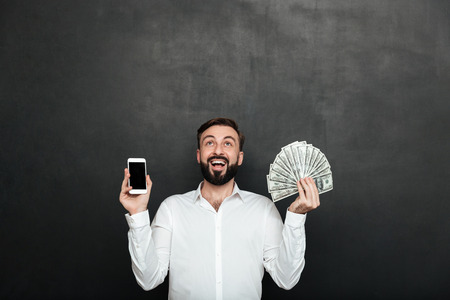Portrait of ecstatic man expressing online earnings with holding lots of money dollar currency and smartphone isolated over dark gray background