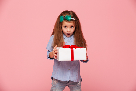 Cute girl 5-6 years holding present box with open mouth, being excited and surprised to get birthday gift over pink background Stock Photo - 95134043