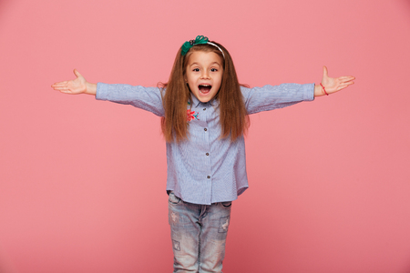 Cheerful little girl in hair hoop posing with open hands against pink background, being friendly and welcoming Banque d'images