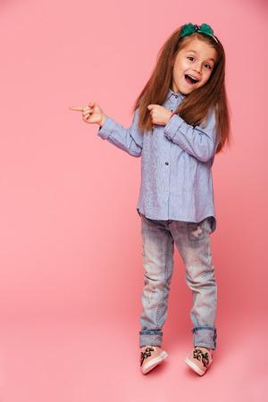 ピンクの背景の上に隔離された人差し指を指す面白い女の子のフルレングス画像、あなたのテキストや製品のためのスペースをコピー