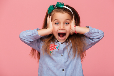 Surprised little girl covering her ears with both hands not listening or overhearing, screaming with open mouth over pink background Foto de archivo