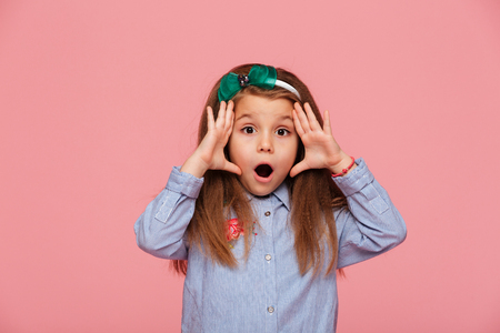 Shot of female kid posing on camera with eyes and mouth wide open being emotional and surprised, over pink background