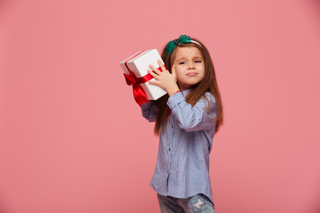 Curious girl 5-6 years shaking present gift-wrapped box close to ear, trying to determine whats inside over pink background Stock Photo