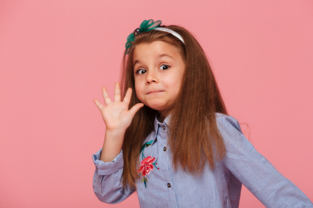 Portrait of funny female kid having long auburn hair looking on camera giving high five, meaning hi or bye with hand over pink background